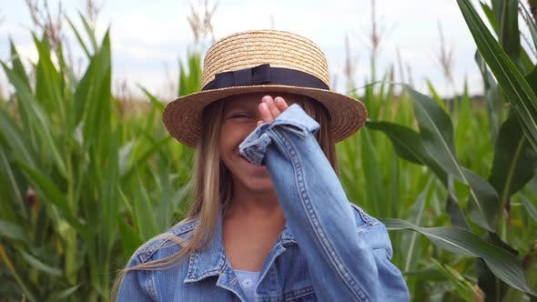 Thumbnail for Portrait of Beautiful Little Girl in Straw Hat Looking Into Camera and Laughs Covering Her Face with