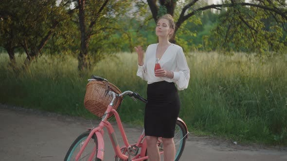 Beautiful Tired Businesslady Standing in Summer Park with Bicycle and Drinking Juice. Portrait of