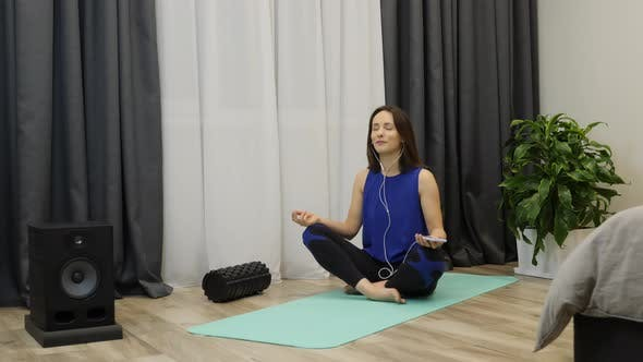Thumbnail for Relaxed concentrated female with closed eyes sitting on yoga mat and enjoying meditation at home