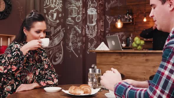 Thumbnail for Gorgeous Couple Drinking Coffee and Eating Croissants in Stylish Hipster Coffee Shop Pub Restaurant