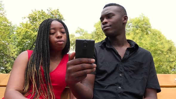 Thumbnail for A Black Man and a Black Woman Sit on a Bench in a Park, Look at a Smartphone and Talk