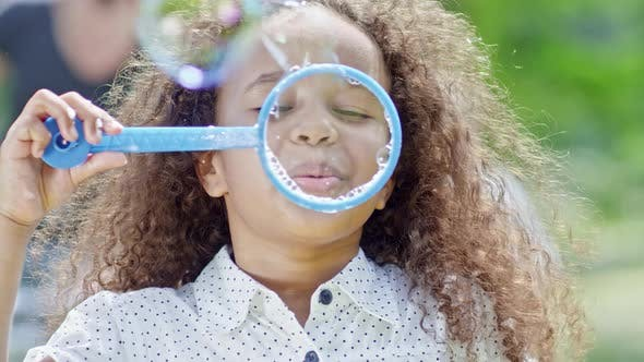 Thumbnail for Little African Girl Blowing Soap Bubbles at Camera