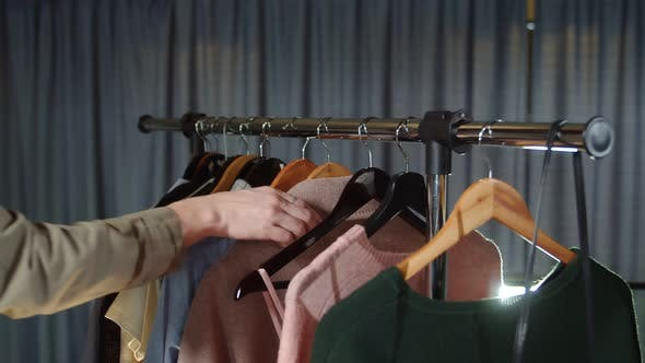 Close Up of Woman Takes a Pink Coat From a Hanger with Clothes
