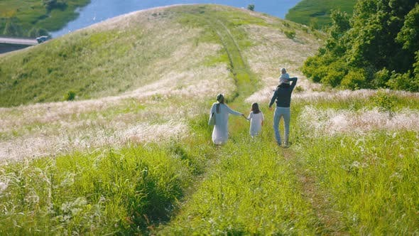 Cover Image for Young Happy Family Walking on the Grassy Path Down the Hill