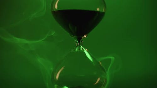 Hour glass on green background