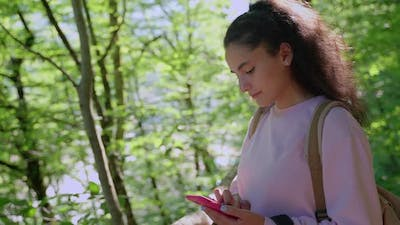 Woman Backpacker with Phone in the Woods
