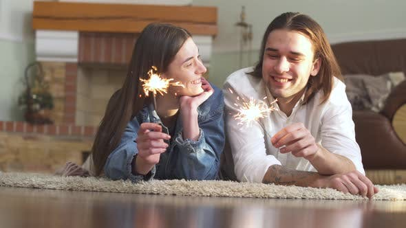 Thumbnail for Joyful Young Beautiful Guy and Girl with Sparklers in Hands Lying on the Carpet