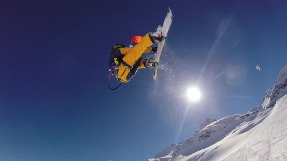 Thumbnail for A young man snow kiting on a snowboard.