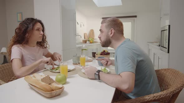 Young Caucasian Couple Eating Meal at Home and Bickering