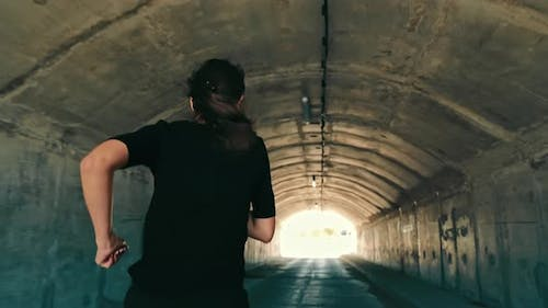 Woman Running in a Dark Tunnel to Meet the Light