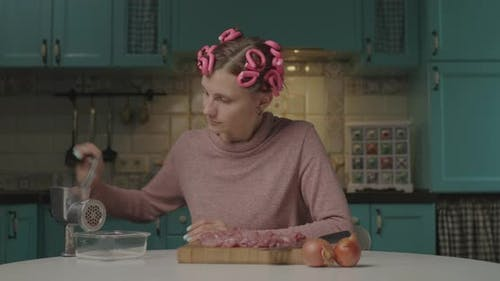 30s Young Woman with Hair Curlers on Head Cooking Meat in Mincer Sitting in the Kitchen. Housewife