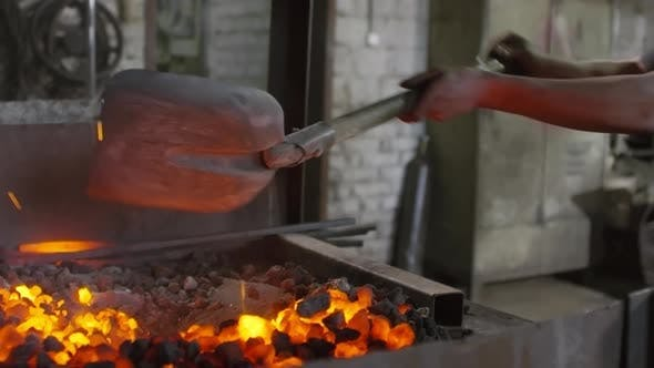 Thumbnail for Man Mixing Coals in Stove with Shovel