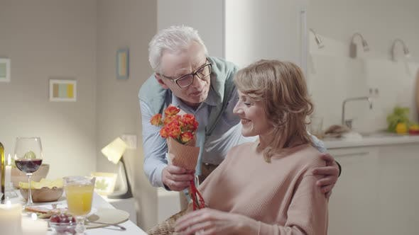 Elderly Man Giving Bouquet of Flowers to Wife at Festive Dinner