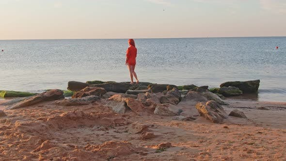 Thumbnail for Lonely Woman in the Red T-shirt Is Standing on Stones at the Shore She Waiting for Sunrise