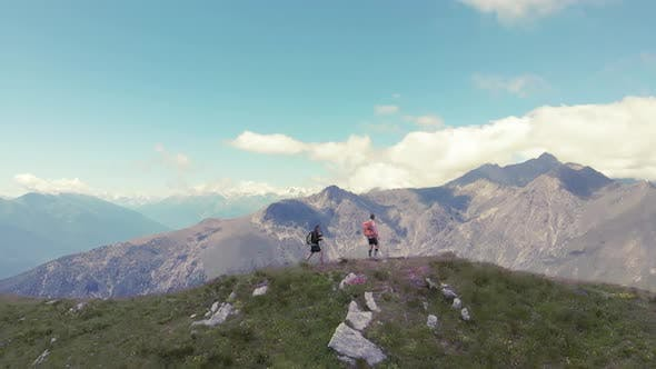 Thumbnail for Aerial slow motion: couple backpackers hiking on mountain top, scenic landscape