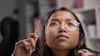 Girl glasses thinking while sitting at classroom