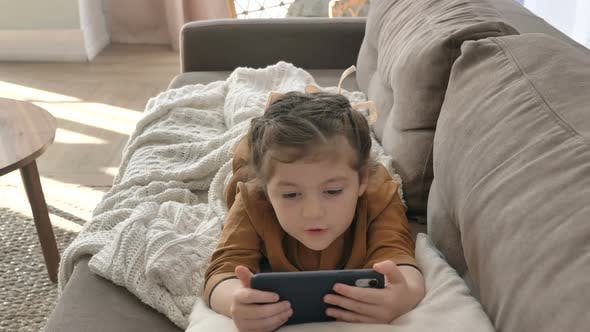 Thumbnail for A Little Girl Is Intently Watching Cartoons on Her Mobile Phone While Lying on the Couch