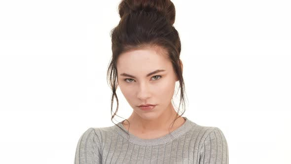 Beautiful Caucasian Brunette Girl Looking Straight at Camera and Pointing to Look Right Into Eyes