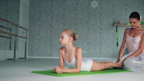 Teacher Helps Preteen Ballerina Do Backbend in Studio