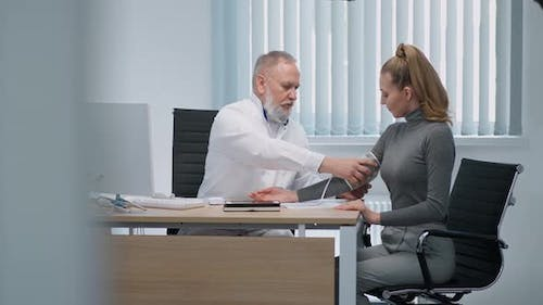 Modern Private Clinic Grayhaired Adult Male Doctor Measures the Blood Pressure of a Young Female