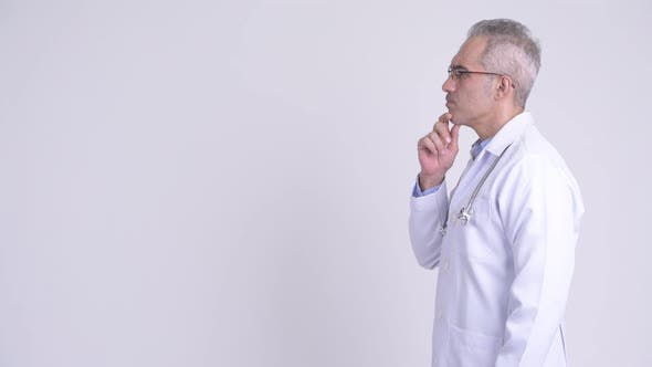 Thumbnail for Profile View of Happy Persian Man Doctor Thinking Against White Background