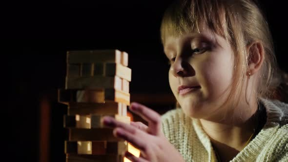 Cover Image for Portrait of A Child Playing a Game Where You Need to Take out Wooden Blocks from The Tower