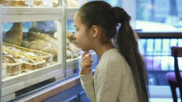 Thumbnail for Cute Little Girl Looking at the Display at the Local Bakery