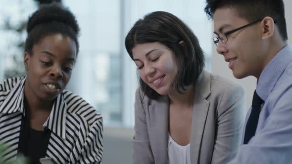 Thumbnail for Multi-Ethnic Coworkers Chatting and Using Smartphone