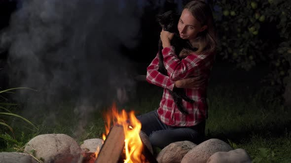 Woman Holds a Cat and Sits Near Campfire at Evening