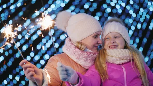 Thumbnail for Mom and Daughter Play Sparklers on the Background of Blurry Christmas Tree Lights