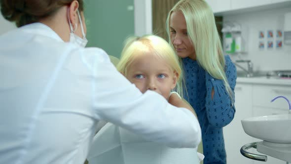 Cover Image for Dentist Fastens a Diaper on a Girl and Takes a Medical Drill