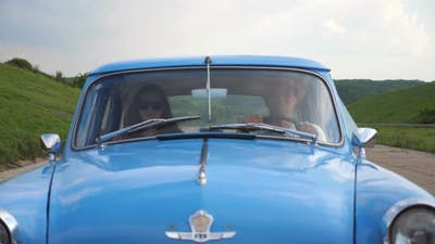 Young Couple in Hats Riding in Vintage Car at Summer Travel