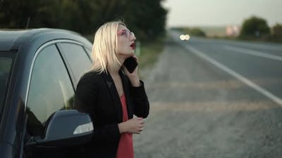 Confused Blonde in Glasses Talks on a Smartphone Emotionally at a Broken Car