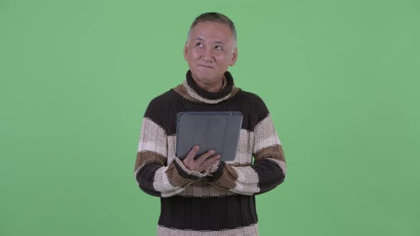 Thumbnail for Happy Mature Japanese Man Thinking While Using Digital Tablet and Talking