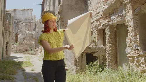 Vertical video of a girl engineer or archaeologist looking at the city destroyed by the earthquake