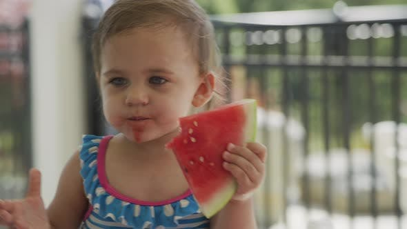 Young girl eating watermelon at backyard barbeque