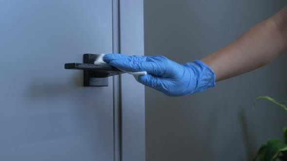 Female hands in rubber medical gloves is disinfecting doorknob. Coronavirus pandemic, covid-19