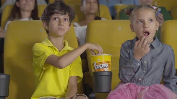 Porträt von aufgeregten nahöstlichen Jungen und kaukasischen Mädchen Filme im Kino und Essen