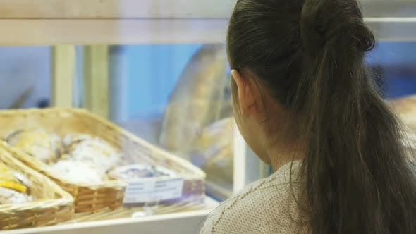 Thumbnail for Cropped Shot of a Cute Little Girl Smiling To the Camera at the Bakery