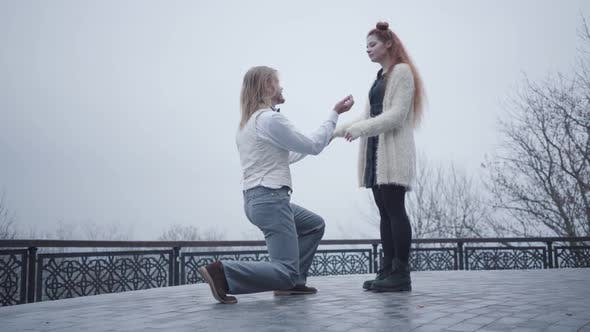 Thumbnail for Side View of Stylish Boy in White Shirt and Vest Standing on One Knee and Proposing To His