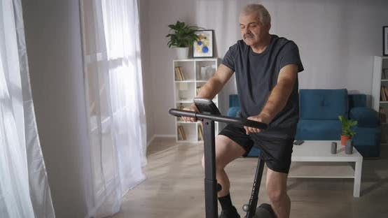 Athletic Middleaged Man Is Training on Exercycle in Living Room Healthy Lifestyle at Isolation