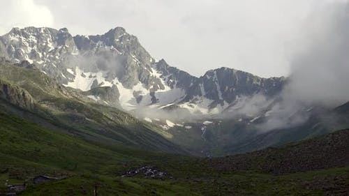High Snowy Mountain Peaks on the Background of Glacial U Valley