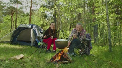 Happy Hiker Couple Roasting Marshmallows on Campfire