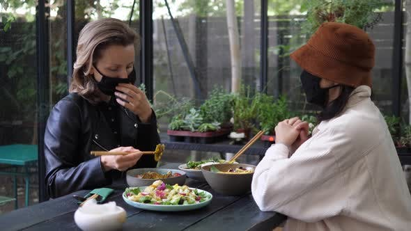 Lunch During Covid-19 Pandemic. Two Girls at the Vegan Restaurant in Face Mask Discussing Something