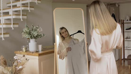 Thumbnail for Sensual Girl With Blond Hair Is Trying On A Silk Dresses In Front Of The Mirror