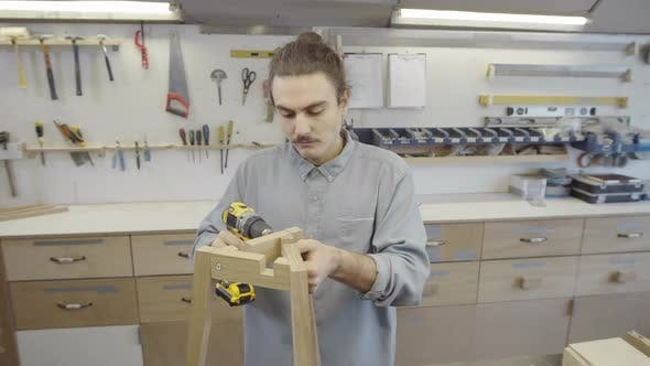 Thumbnail for Young Artisan Tightening Screws on Handmade Wooden Table at Workshop