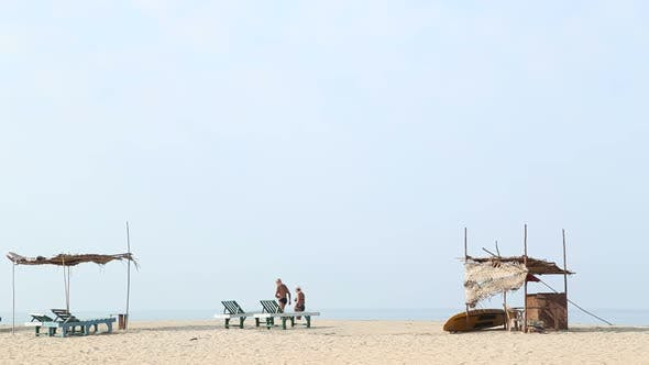 Thumbnail for Man passing next to deck chairs at beach in Goa.