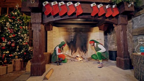 Elves near fireplace on Christmas background indoors. Funny elves in green costumes sit