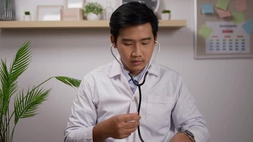 Doctor cardiologist wearing white medical coat showing stethoscope and looking at camera