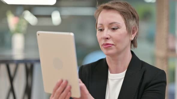 Attractive Old Businesswoman Using Tablet